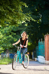 Smiling young female in casual clothes riding blue bike in beautiful park on sunny summer day. Attractive woman red purse vintage turquoise bicycle green trees historical fence.