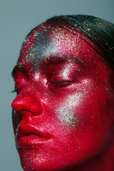 Close up of a portrait of the girl with an unusual make-up showing space. Gloss and shine, stars and constellations on a face. Body art, studio of beauty and art