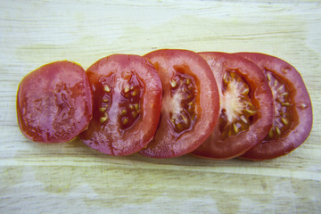 Sliced tomatoes laying on wooden desk. Red tomatos.