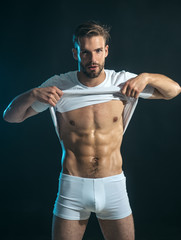 Handsome man, unshaven, seductive macho, bodybuilder, with stylish hairstyle, haircut, removes white t-shirt, showing sexy, muscular torso, six packs abs, male striptease on dark background.