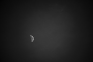 A vaguely illuminated moon on a dark background