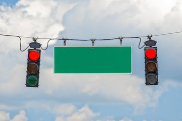 Horizontal shot of two red traffic lights hanging from a cable with a blank street sign in-between with blue sky and clouds behind it.