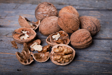heap of cracked and whole walnuts on wooden background
