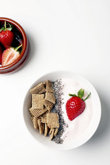 Overhead view of breakfast with strawberries over white background