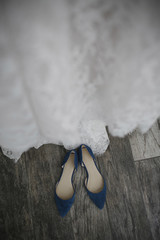 High angle view of wedding dress and sandals on hardwood floor at wedding ceremony