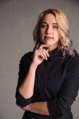 portrait of serious young woman with colored hair in black shirt isolated on gray studio background posing to the camera, bussines woman
