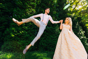 a pretty girl in a long dress holds the hand of her boyfriend who funny jumping against the background of the trees