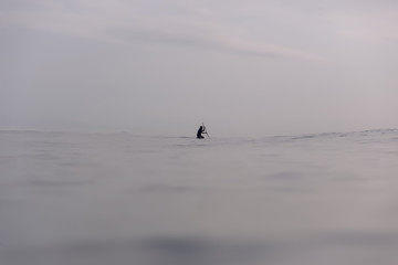 Mid distance view of silhouette man paddleboarding in sea against sky