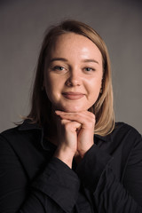 portrait of smiling young woman in black shirt isolated on gray studio background posing to the camera