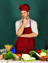Cook or chef with thoughtful face stands by vegetables
