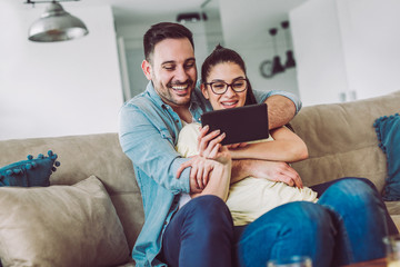 Tender smiling couple with digital tablet sitting on sofa at home
