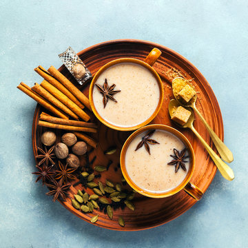 Masala tea chai latte traditional hot Indian teatime ceremony sweet milk with spices, herbs organic infusion healthy beverage in porcelain cup on blue table background