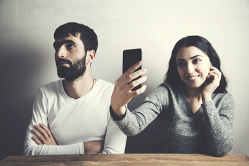 young attractive couple with woman taking selfie