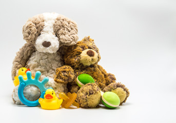 2 toy teddy bears with a baby rattle, pacifier, teething ring and 2 rubber duckies isolated on a solid background