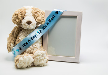 'It's A Boy' blue satin ribbon on stuffed teddy bear with empty picture frame to customize with photo