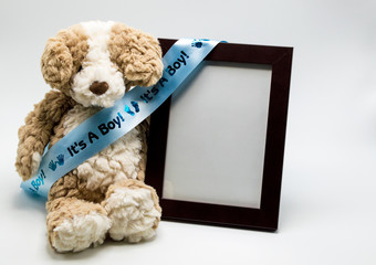 'It's A Boy' blue satin ribbon on a stuffed teddy bear with an empty picture frame to personalize with photo