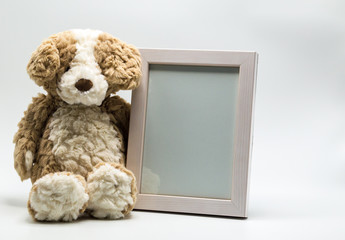 plush toy teddy bear and empty picture frame to customize with photo isolated on solid background
