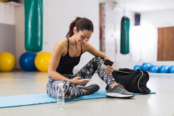 Young woman eating chocolate while taking a break in gym
