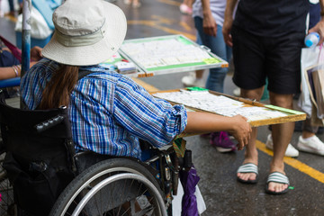 Girls sit the wheelchair and sell government's lottery at a street market of Bangkok Thailand.