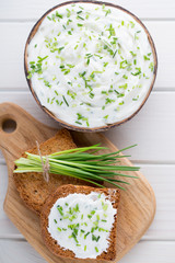 Bowl of cream cheese with green onions, dip sauce on wooden table.