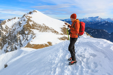 The mountaineer photographing with the mobile phone on the top of the ridge of the Begunjscica mountain, Slovenia