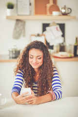 Smiling woman holding her cellphone in the kitchen. Smiling woman