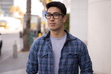 Young Asian man walking street serious face