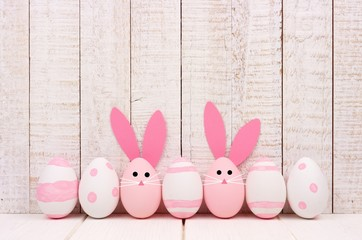 Row of Easter eggs against a white wood background. Two with bunny faces and ears.