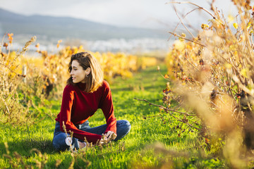 Young beautiful girl in the field. She wears a red sweater and jeans.