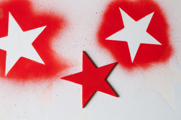 Textured background with white star shapes on red paint with red splatter and wooden red star