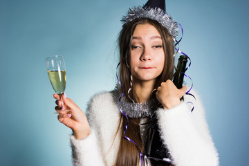 drunk woman in a festive cap holding champagne in hands