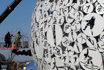 Workers are pictured at the base of the Olympic Cauldron for the upcoming 2018 Pyeongchang Winter Olympic Games at the Alpensia resort in Pyeongchang
