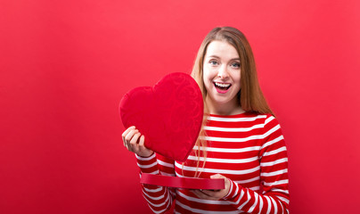 Happy young woman holding a big heart gift box on a red background