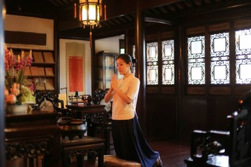 a woman in traditional Chinese costume is praying in a traditional traditional Chinese room