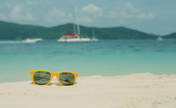 Bright orange Fashion sunglasses on the white sand of a tropical beach. Vintage look. Travel and vacation concept. with copy space