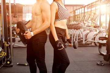 Cropped shot of a young man and woman working out at the gym