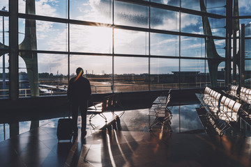 Backlighted silhouette of man traveler with his luggage standing alone next to giant windows inside of contemporary airport departure area near empty rows of wooden seats and waiting for his flight