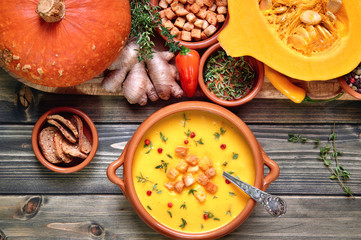 Pumpkin soup in ceramic bowl on rustic wood served with thyme and croutons. Next to it is a tray with healthy soup ingredients. Flat lay, view from above.