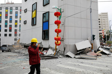 A man walks past debris outside a damaged hotel after an earthquake hit Hualien