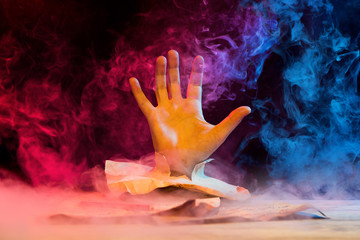 hand reaching out from vintage paper on smoky colorful background