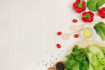 Fresh green vegetables, greens, red cherry tomatoes and kitchenware on soft white wood board, border, top view.