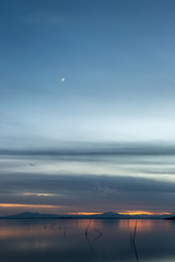 Beautiful view of Trasimeno lake (Umbria, Italy) at dusk, with blue and orange tones and moon in the sky