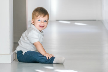Smiling blue-eyed boy baby in a white polo shirt and jeans sitting on the floor