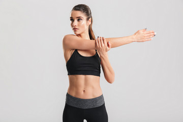 Image of slim sporty woman doing fitness and stretching her body, isolated over gray background