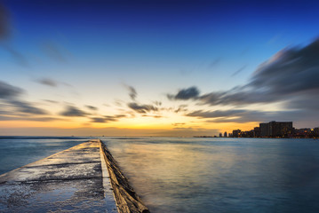 Long exposure at sunset of cement pier jutting out into Pacific Ocean during sunset golden hour