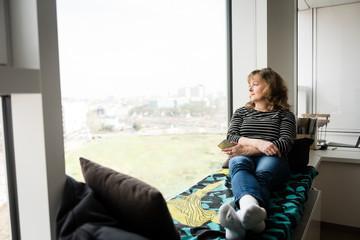 Woman sitting alone near big window at home