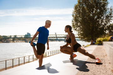 Athletic couple stretching outdoor near river