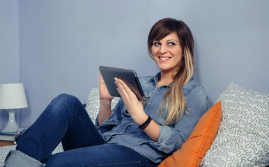 Portrait of happy beautiful woman using electronic tablet and resting over a bed. Leisure time at home concept.
