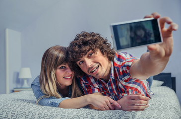 Happy young couple in love taking a selfie with smartphone lying over a bed. Leisure time at home concept.