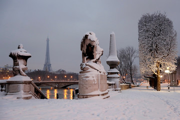A view shows the snow-covered Pont Alexandre III bridge witht the Eiffel tower in the background in the early morning in Paris